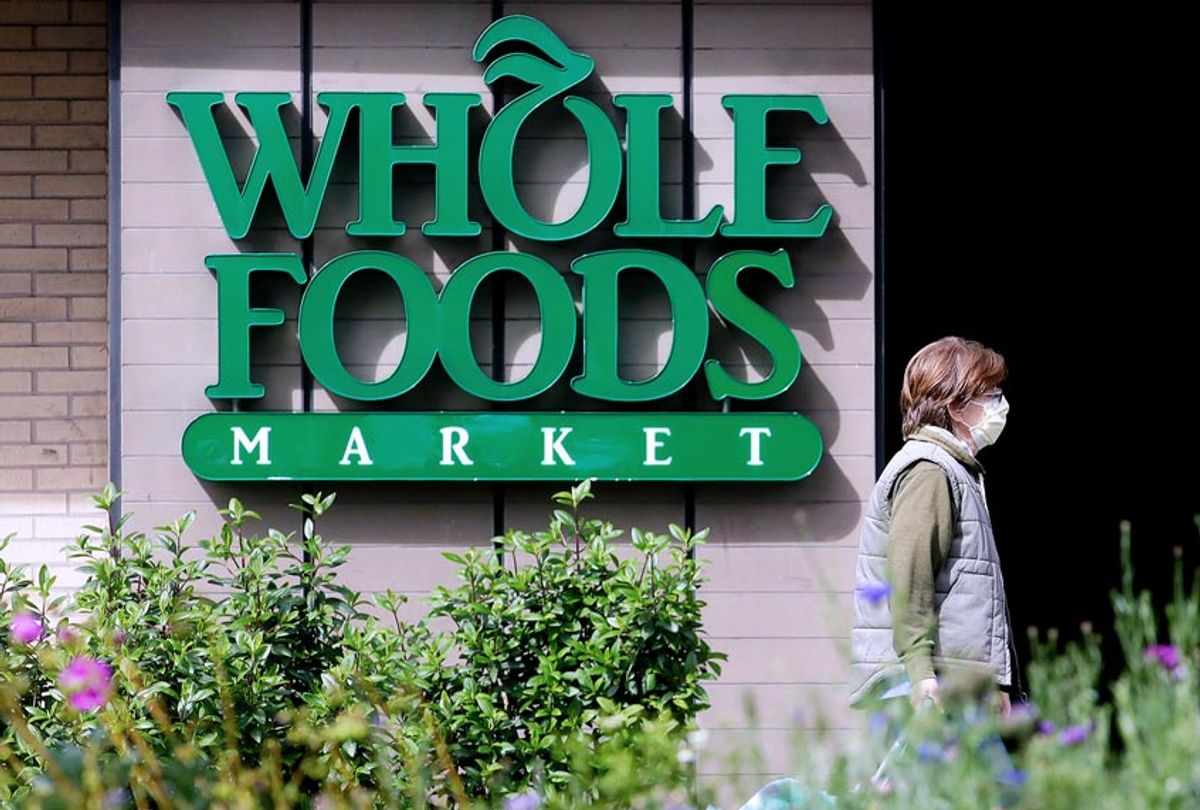 A pedestrian wears a mask while walking past a sign for a Whole Foods Market in San Francisco, Tuesday, March 31, 2020. (AP Photo/Jeff Chiu)