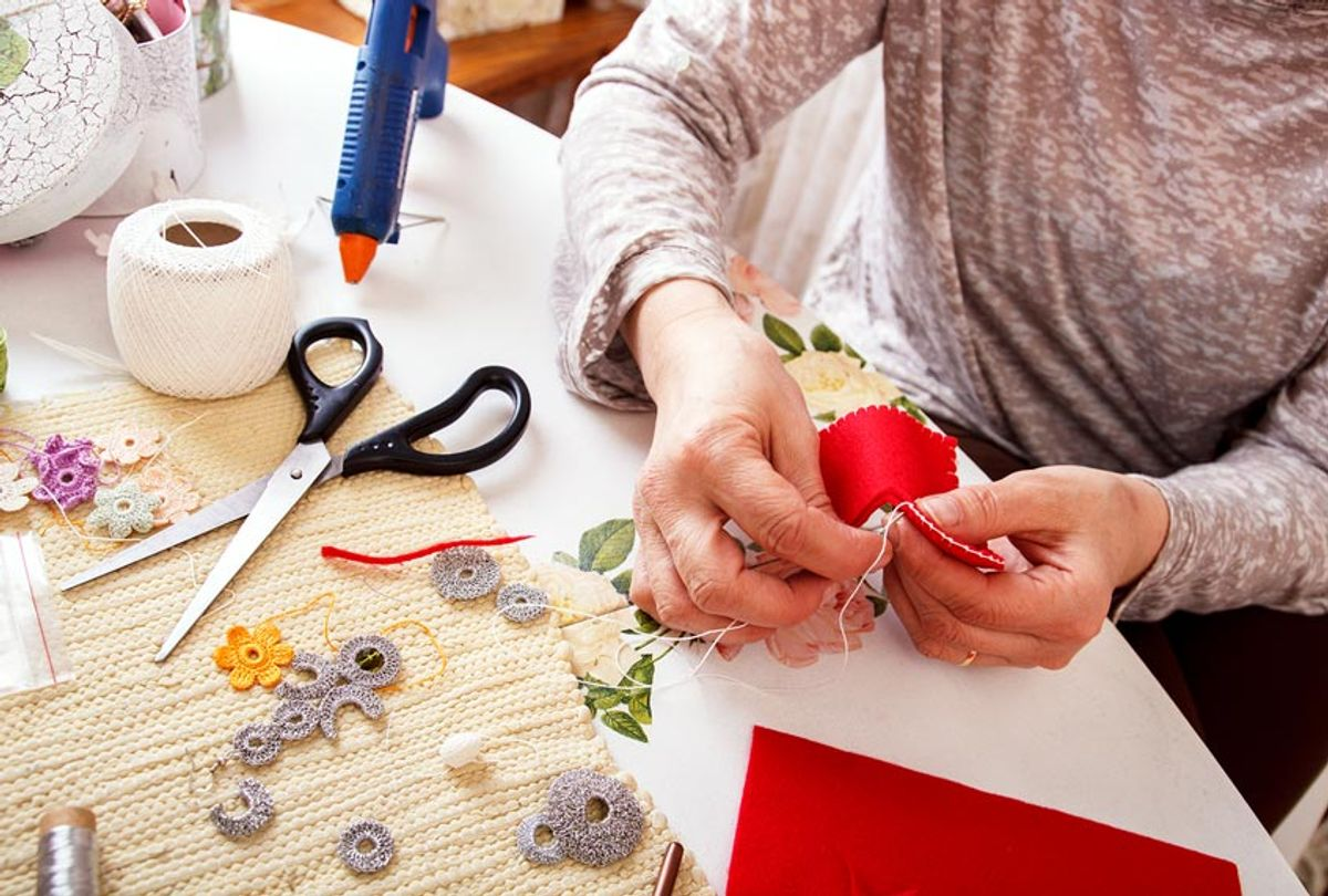 A woman sews by hand and making an ornament (Getty Images)