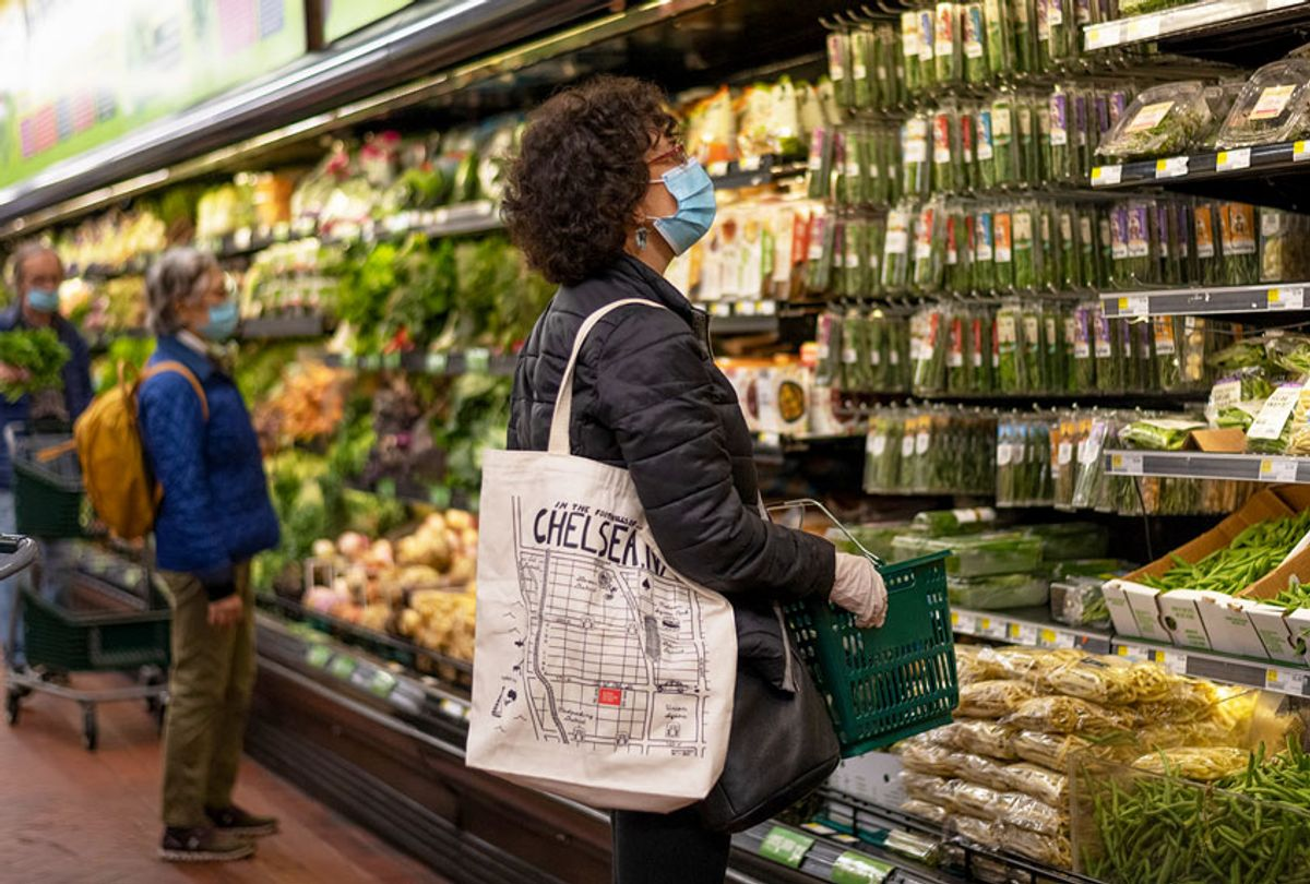 A woman wearing a mask and gloves shops at grocery store amid the coronavirus pandemic (Alexi Rosenfeld/Getty Images)