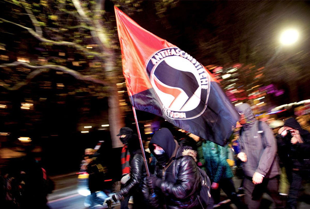 A Man charges with an Anti-Fascist flag (Getty Images)
