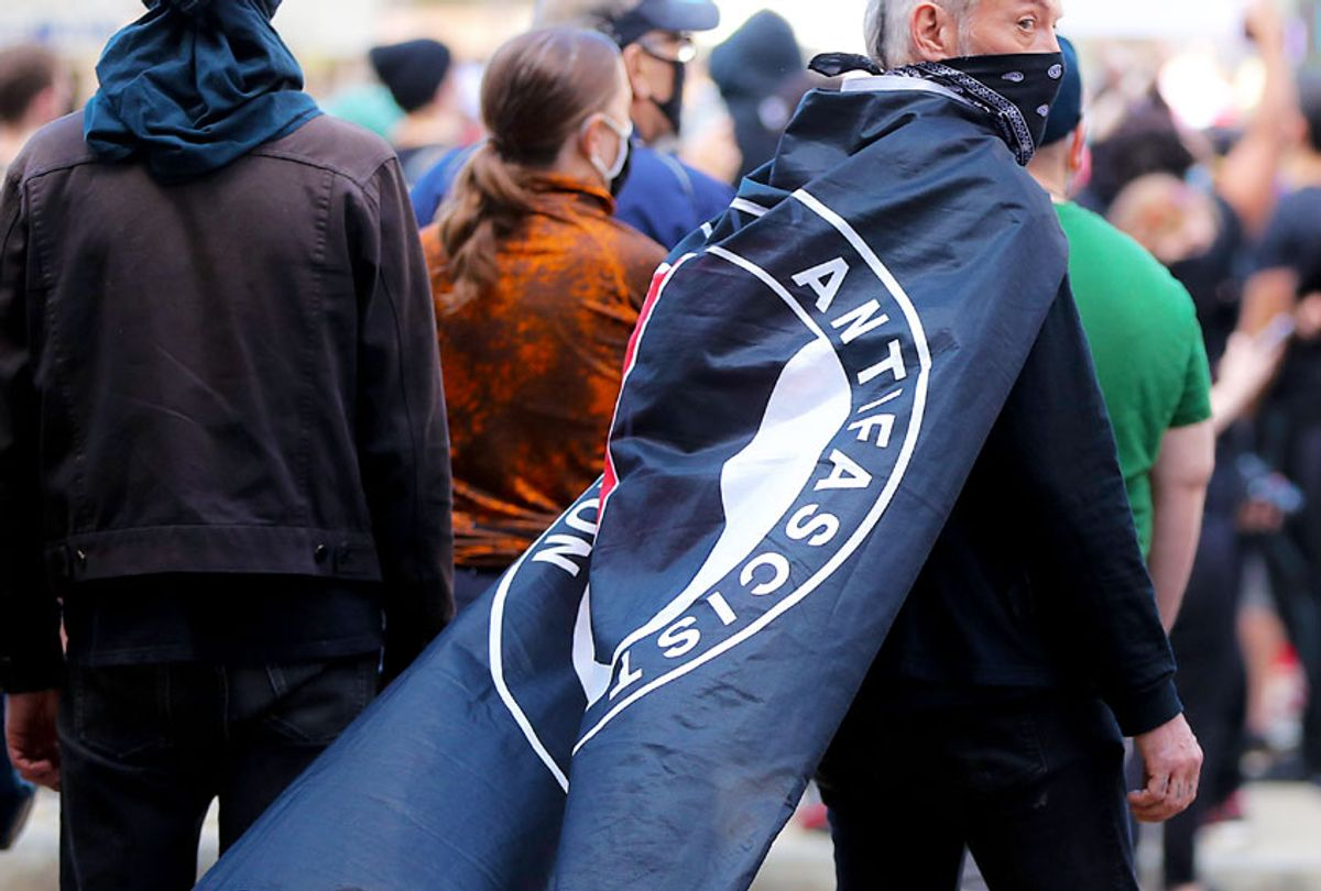 Protester with an ANTIFA flag draped over his shoulders during a rally (Matthew J. Lee/The Boston Globe via Getty Images)