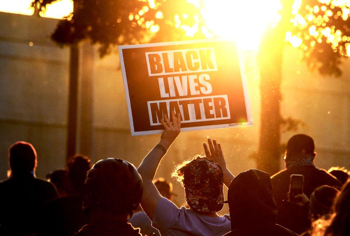 A protestor holds a Black Lives Matter placard (CHANDAN KHANNA/AFP via Getty Images)