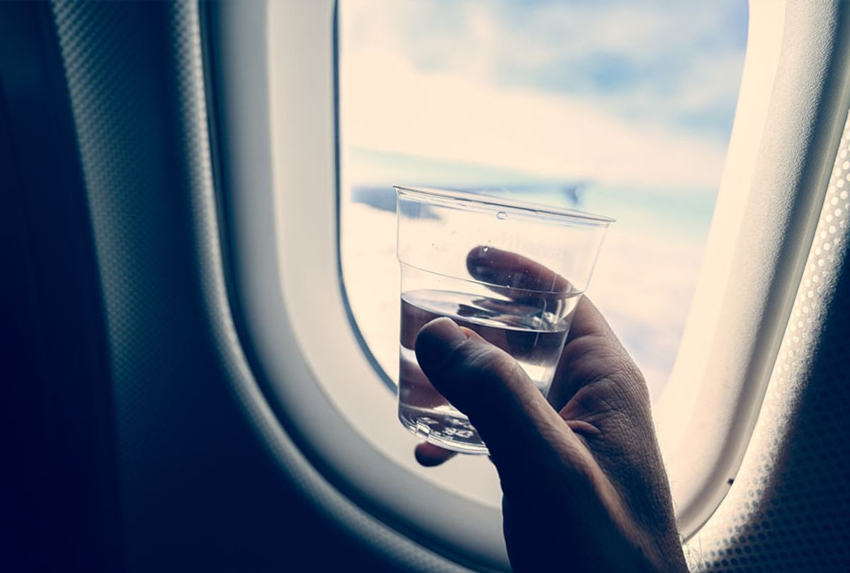 Man's hand holding a glass with transparent liquid (water or liquor), inside an airplane (Getty Images)