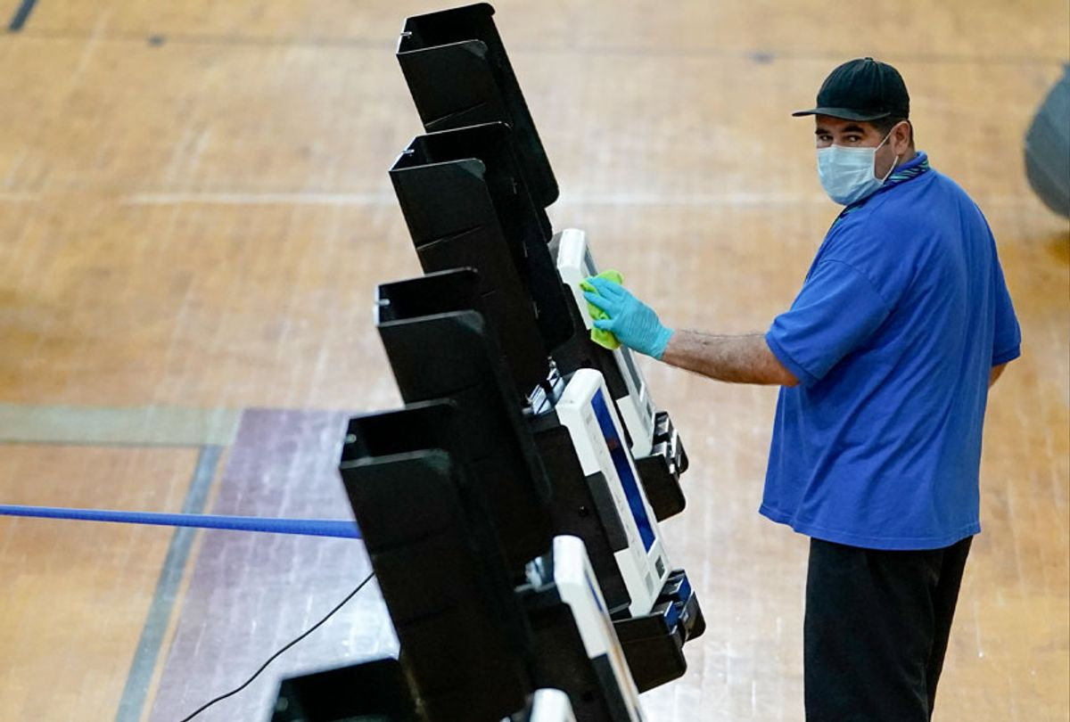 A worker cleans a voting machine after it was used at McKinley Technology High School on primary election day on June 2, 2020 in Washington, DC. On Tuesday, nine states and the District of Columbia are holding primaries, most of which were previously delayed due to the coronavirus pandemic. (Drew Angerer/Getty Images)