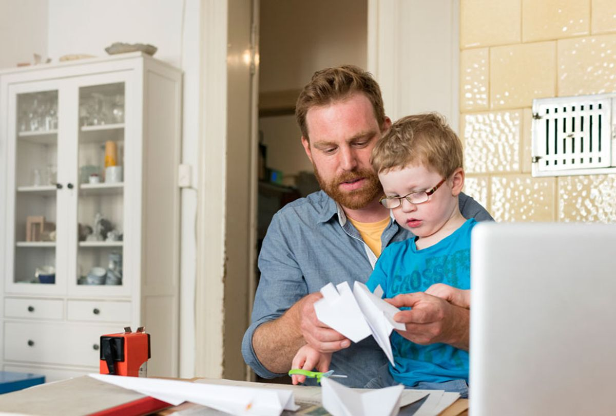 Father and toddler son making paper plane at home  (Getty Images)