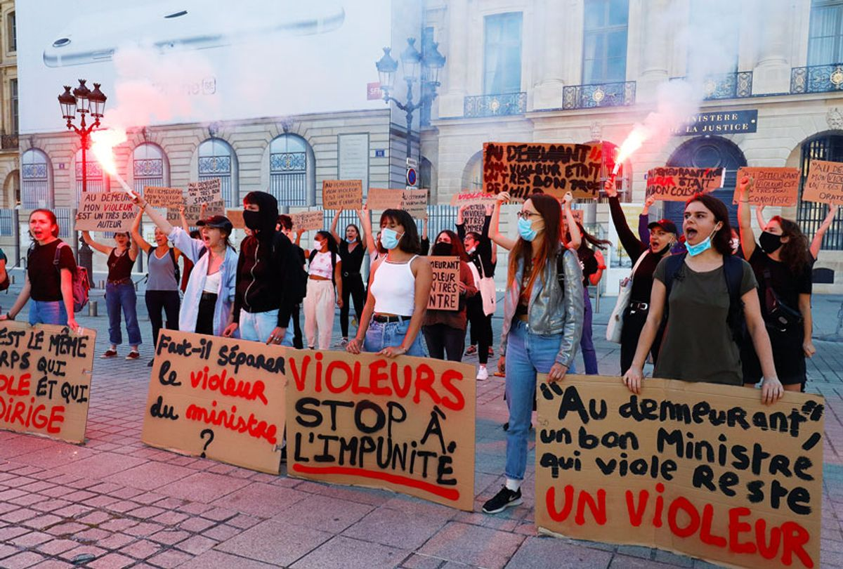"""Women hold flares and placards during a protest called by """"Collages Feminicides Paris"""" feminist organization in front of the Ministry of Justice on Place Vendome in Paris, on June 22, 2020. (FRANCOIS GUILLOT/AFP via Getty Images)"""
