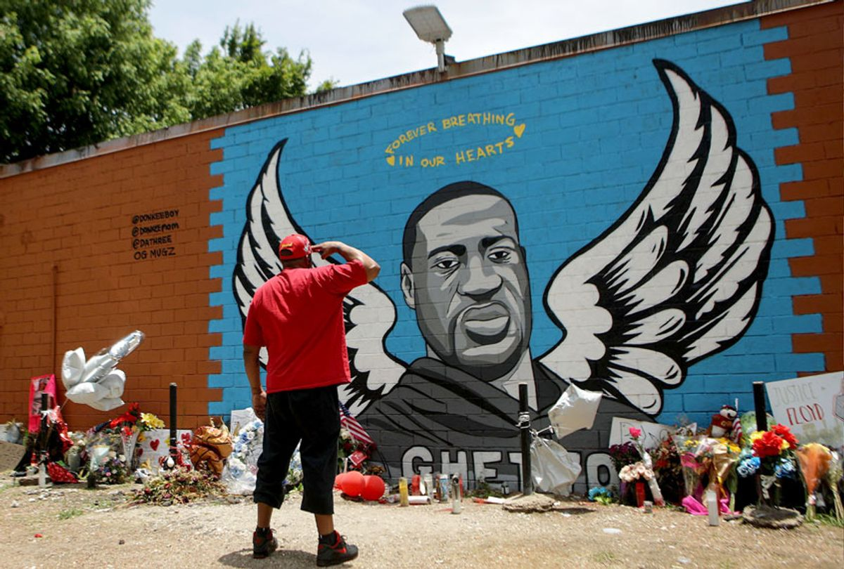 A man salutes at a mural dedicated to George Floyd, across the street from the Cuney Homes housing project in Houston's Third Ward, where Floyd grew up and later mentored young men, on June 10, 2020 in Houston, Texas. (Mario Tama/Getty Images)
