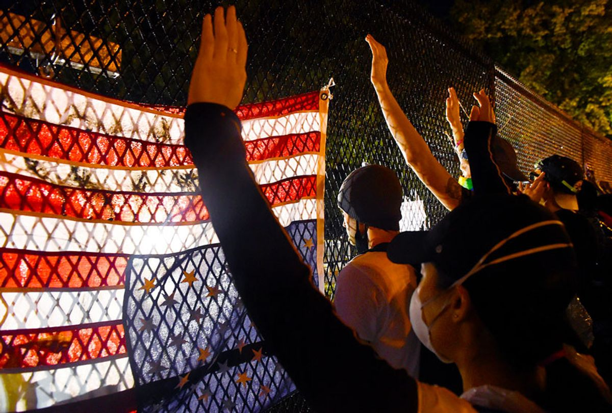 Protesters hold up their hands in front of a recently erected metal fence in front of Lafayette Square near the White House to keep protestors at bay on June 4, 2020 in Washington, DC. (OLIVIER DOULIERY/AFP via Getty Images)