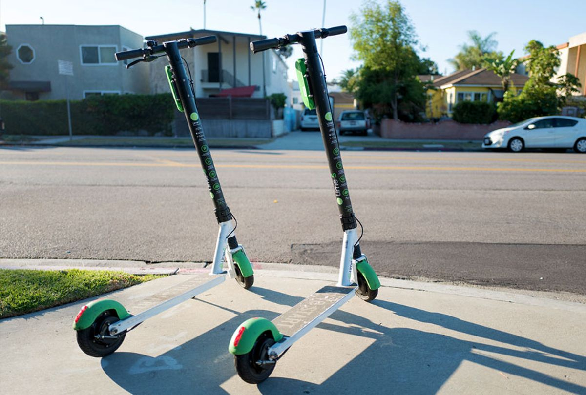"""Two scooters from dockless electric scooter sharing economy company Lime are parked in a """"hub"""" near a road in the Marina Del Rey neighborhood of Los Angeles, California (Smith Collection/Gado/Getty Images)"""
