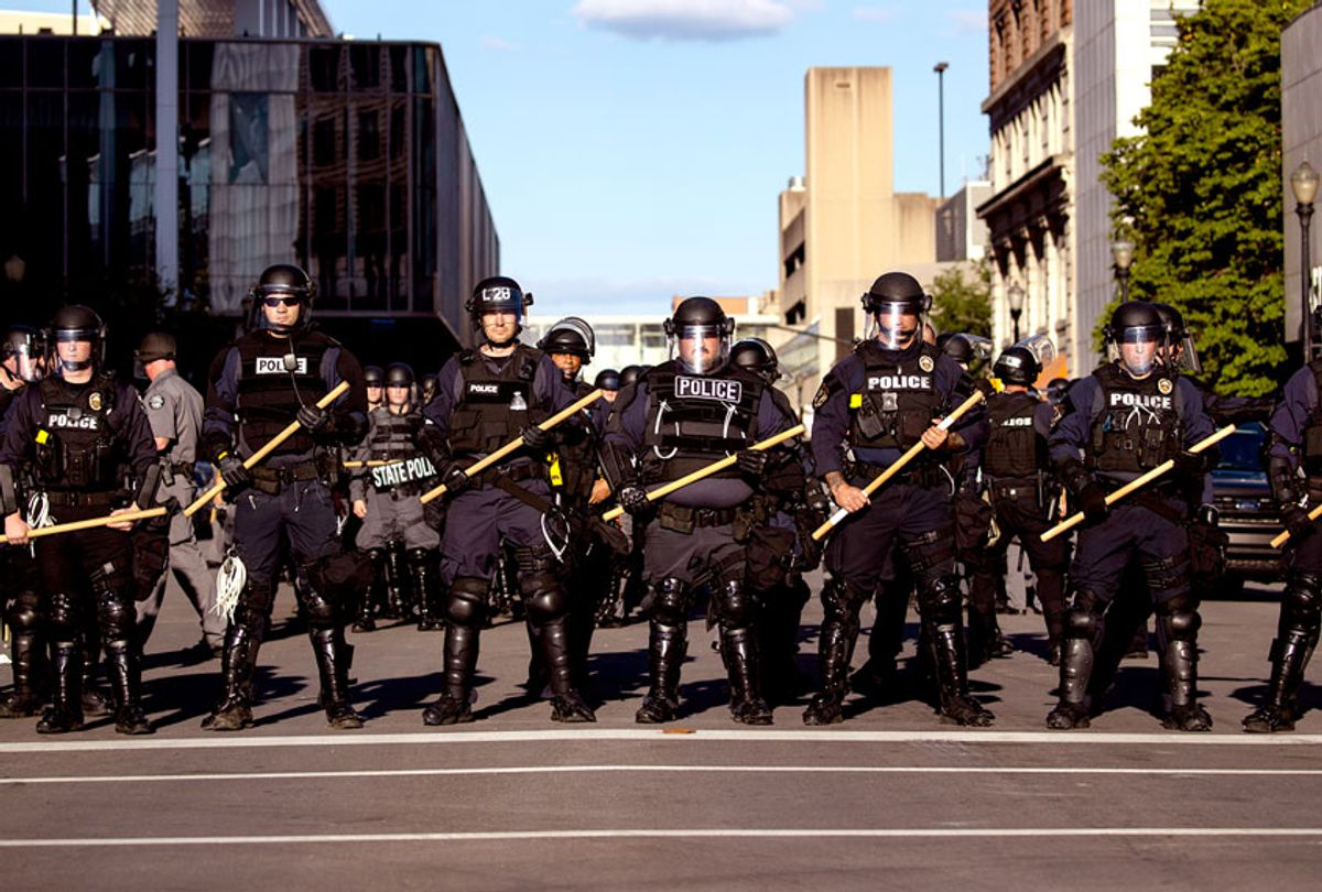 Police officers in riot gear stand in formation at a cross street as they make their way to where protesters are gathered on May 30, 2020 in Louisville, Kentucky. Protests have erupted after recent police-related incidents resulting in the deaths of African-Americans Breonna Taylor in Louisville and George Floyd in Minneapolis, Minnesota. (Brett Carlsen/Getty Images)