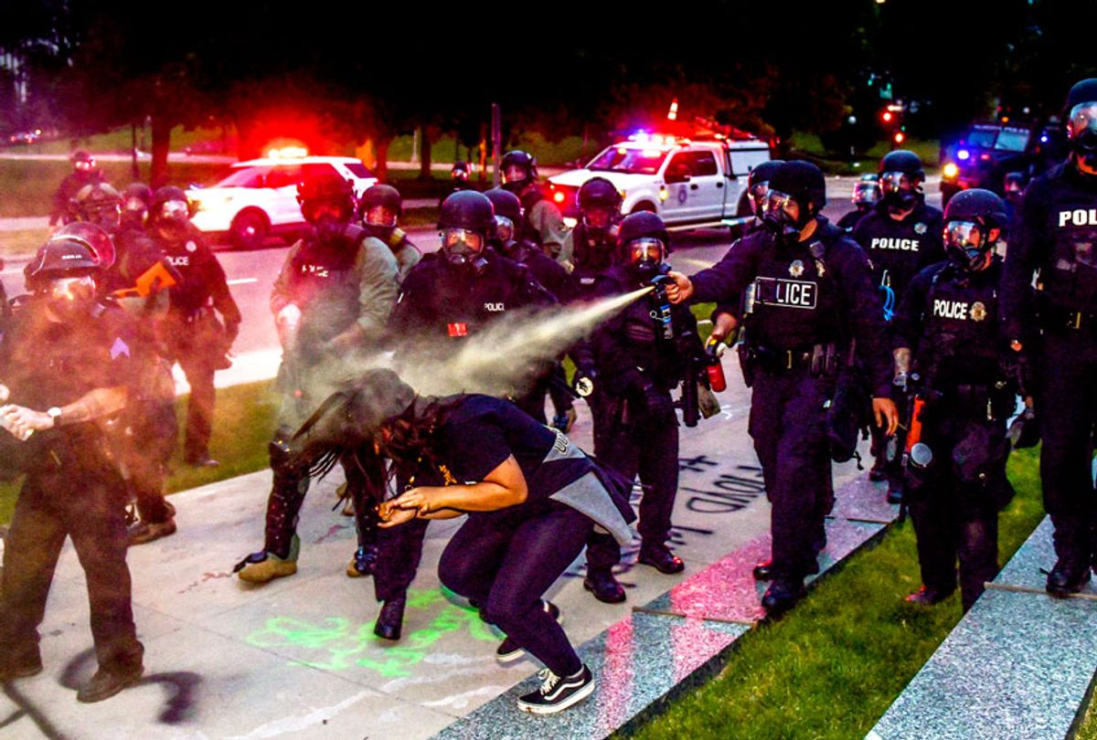 Police officers pepper spray a woman next to the Colorado State Capitol as protests against the death of George Floyd continue (Michael Ciaglo/Getty Images)