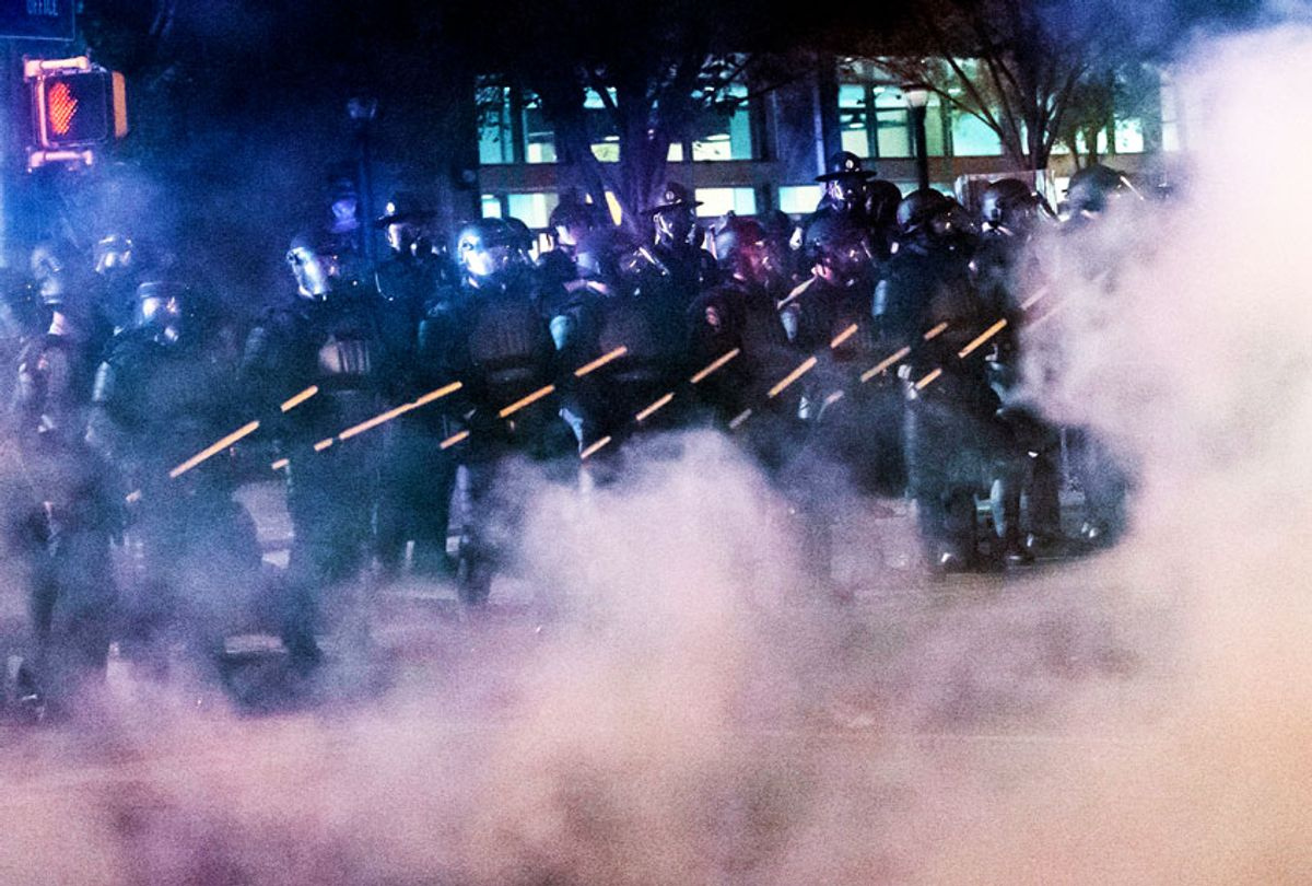 Police in riot gear stand near Centennial Olympic Park during rioting and protests in Atlanta (JOHN AMIS/AFP via Getty Images)