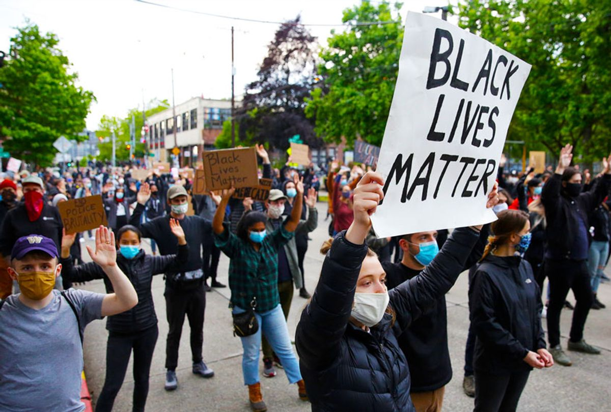 People hold up placards to protest over the death of George Floyd, outside the Seattle Police Department's East Precinct in Seattle, Washington (JASON REDMOND/AFP via Getty Images)