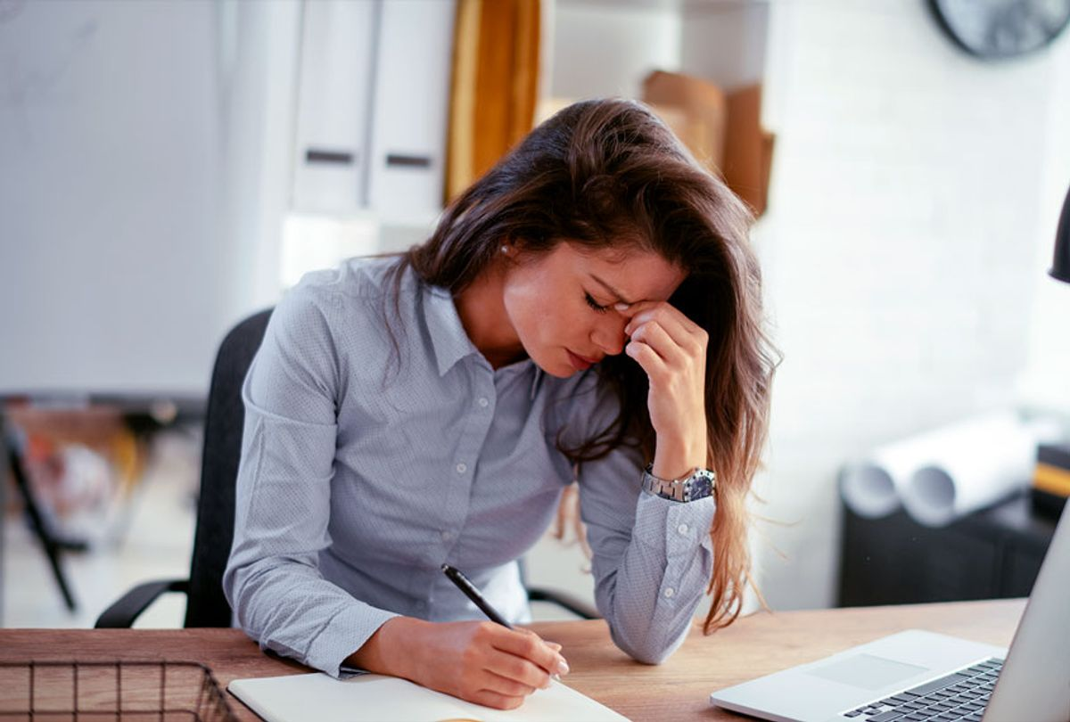 Exhausted businesswoman having a headache at her desk (Getty Images)