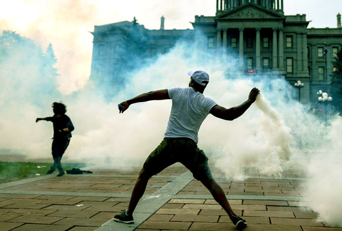 A man throws a tear gas canister back at police officers in front of the Colorado State Capitol as protests against the death of George Floyd continue (Getty Images/Michael Ciaglo)