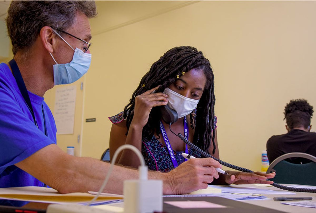 Michael Spatz, L, a volunteer with the Alexandria medical reserve corps, helps AshaLetia Henderson through her first positive-case call as a coronavirus contact tracer, where the Alexandria Health Department set up offices for coronavirus contact tracing and investigations at the Oswald Durant Arts Center in Alexandria, VA, on Wednesday, June 24, 2020. (Jahi Chikwendiu/The Washington Post via Getty Images)