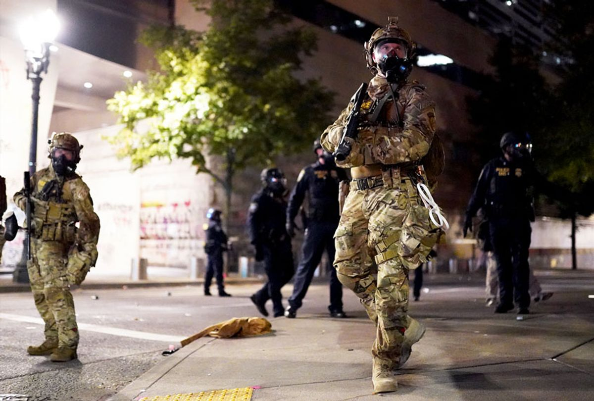 A federal officer watches a crowd of protesters during a standoff between the two groups at the Mark O. Hatfield U.S. Courthouse on July 21, 2020 in Portland, Oregon. State and elected officials have called for the federal officers to leave Portland as clashes between protesters and federal police continue to escalate. (Nathan Howard/Getty Images)