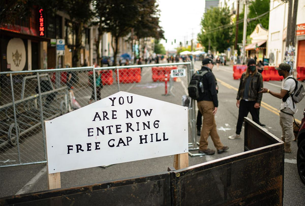"""A sign is seen on a barrier at an entrance to the so-called """"Capitol Hill Autonomous Zone"""" on June 10, 2020 in Seattle, Washington. The zone includes the blocks surrounding the Seattle Police Departments East Precinct, which was the site of violent clashes with Black Lives Matter protesters, who have continued to demonstrate in the wake of George Floyd's death. (David Ryder/Getty Images)"""