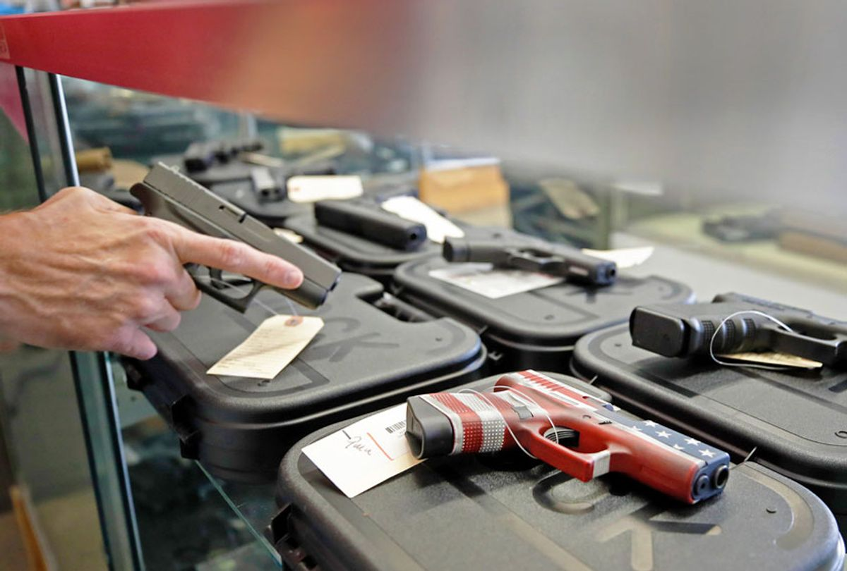 A worker restocks handguns at Davidson Defense in Orem, Utah on March 20, 2020. - Gun stores in the US are reporting a surge in sales of firearms as coronavirus fears trigger personal safety concerns. (GEORGE FREY/AFP via Getty Images)