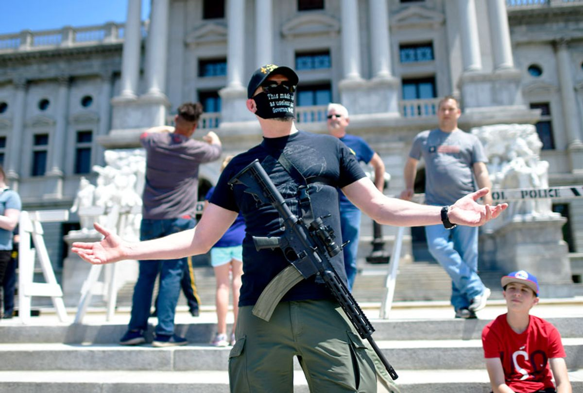 A man with an assault rifle reacts while joining demonstrators outside the Pennsylvania Capitol Building to protest the continued closure of businesses due to the coronavirus pandemic on May 15, 2020 in Harrisburg, Pennsylvania. Pennsylvania Governor Tom Wolf has introduced a color tiered strategy to reopen the state with most areas not easing restrictions until June 4. (Mark Makela/Getty Images)