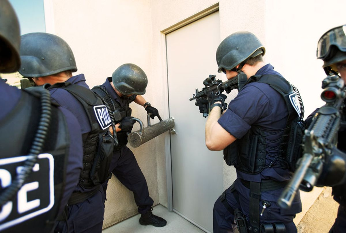 Police officers breaking down doors (Getty Images)
