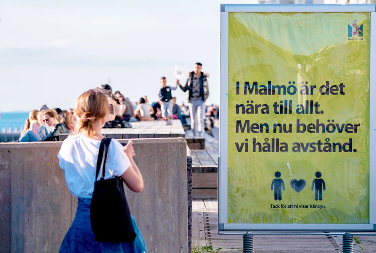 People enjoy the warm evening at Sundspromenaden in Malmo, Sweden, on May 26, 2020, amid the coronavirus pandemic. - The sign reads 'In Malmo everything is near. But now, we need to keep distance'. (JOHAN NILSSON/TT News Agency/AFP via Getty Images)