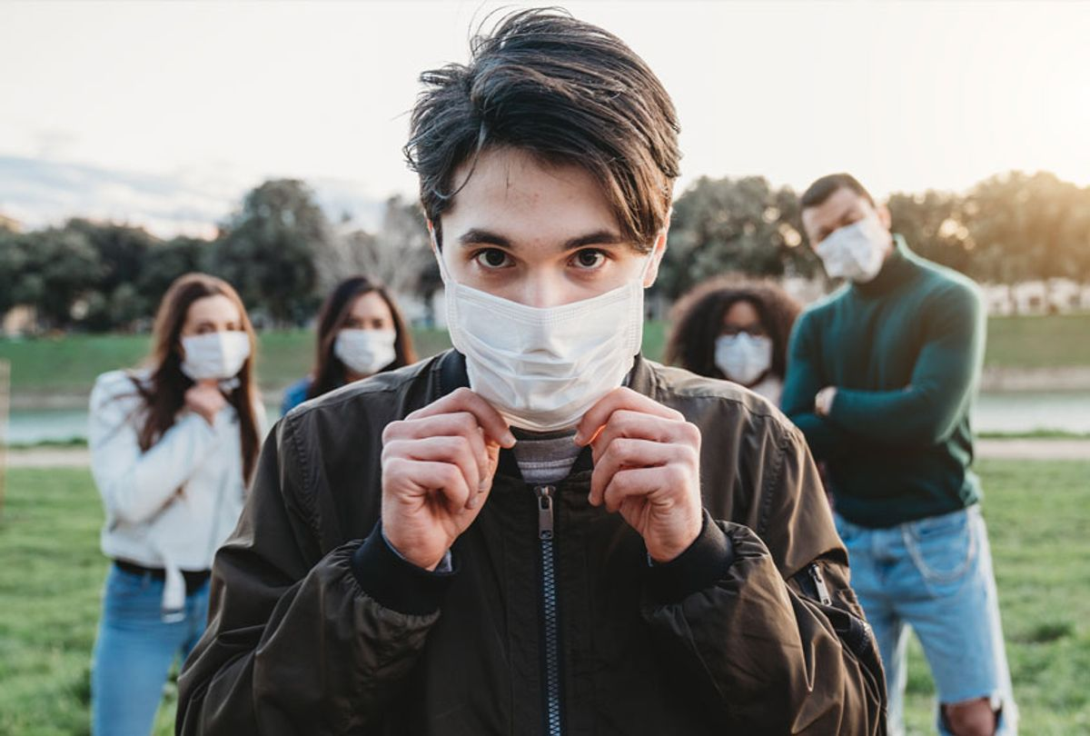 Young adult man wearing a pollution mask to protect himself from viruses. His friends are in the background. They all are wearing masks. (Getty Images)