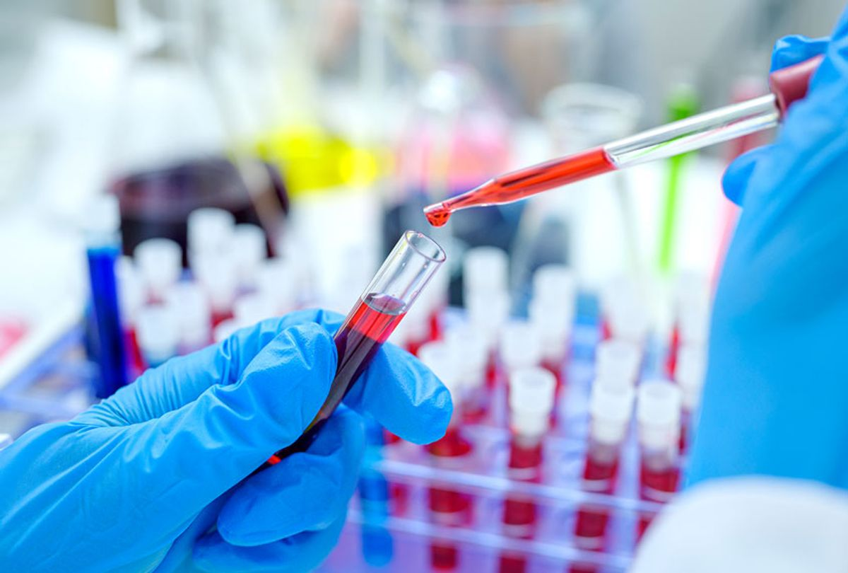 Scientist hand holding test tube with blood in laboratory. (Getty Images)