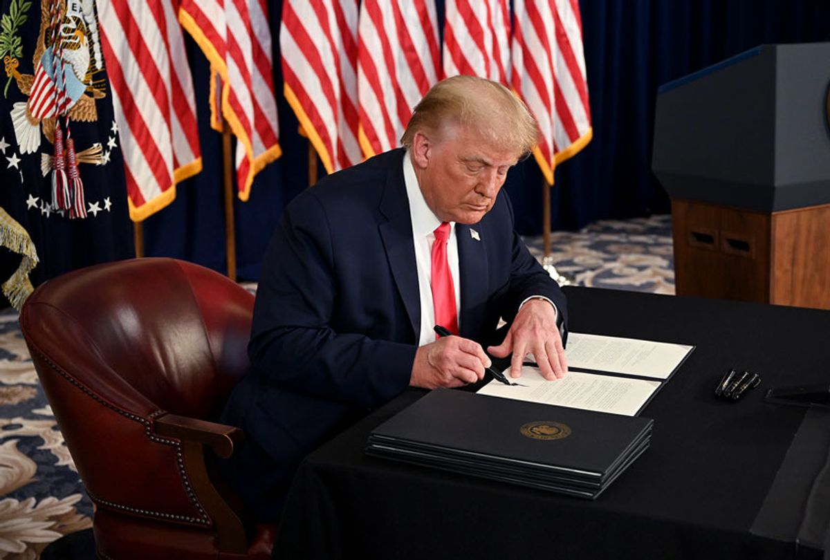 US President Donald Trump signs executive orders extending coronavirus economic relief, during a news conference in Bedminster, New Jersey, on August 8, 2020. (JIM WATSON/AFP via Getty Images)