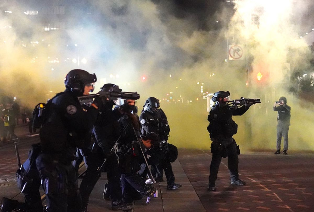 Portland police officers fires less lethal rounds through smoke while dispersing a crowd of about 150 people from Portland City Hall on August 25, 2020 in Portland, Oregon. Crowds chanted in support of Kenosha Wisconsin on the 90th night of protests Tuesday, where demonstrations have continued for days following the police shooting of Jacob Blake. (Nathan Howard/Getty Images)