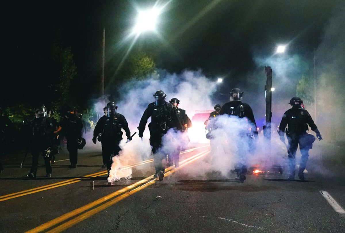 Portland police officers walk through clouds of smoke while dispersing a crowd from in front of the Multnomah County Sheriffs Office on August 22, 2020 in Portland, Oregon. Hundreds of protesters clashed with police Saturday night following a rally in east Portland. (Nathan Howard/Getty Images)