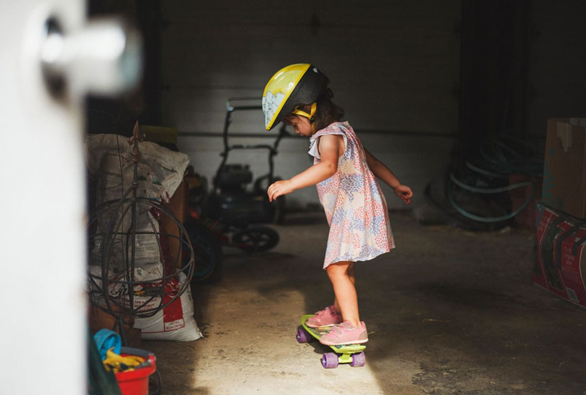 Side view of girl wearing helmet while standing on skateboard in garage (Getty Images)