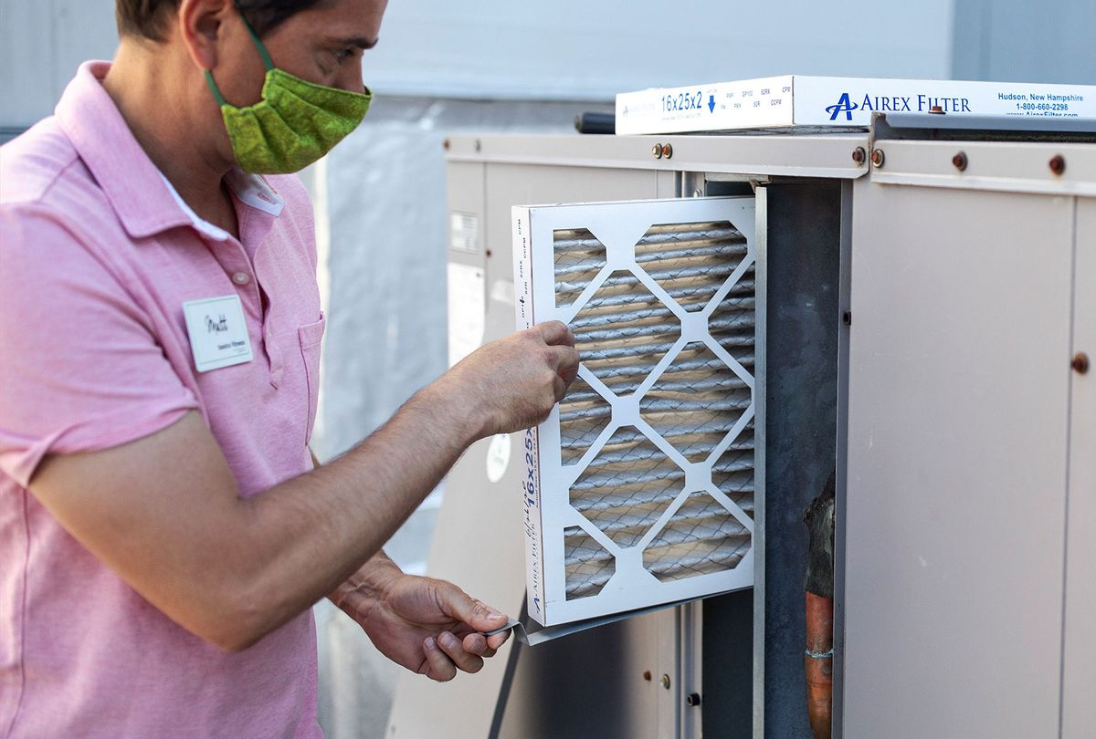 Mark Marston slides a MERV 13 air filtration filter back into the HVAC system outside of this gym Basics Fitness Center on Tuesday, July 21, 2020. (Brianna Soukup/Portland Press Herald via Getty Images)