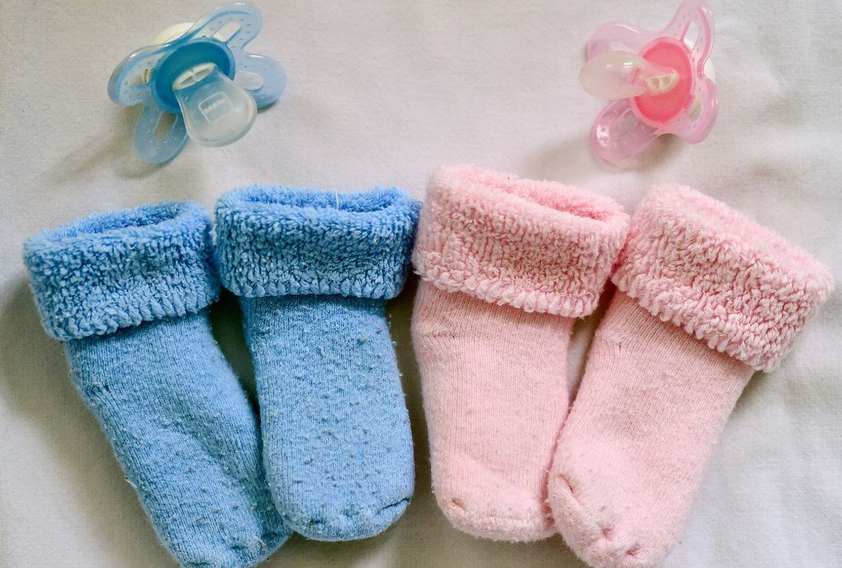 Blue and pink baby booties and pacifiers (Patrick Pleul/picture alliance via Getty Images)
