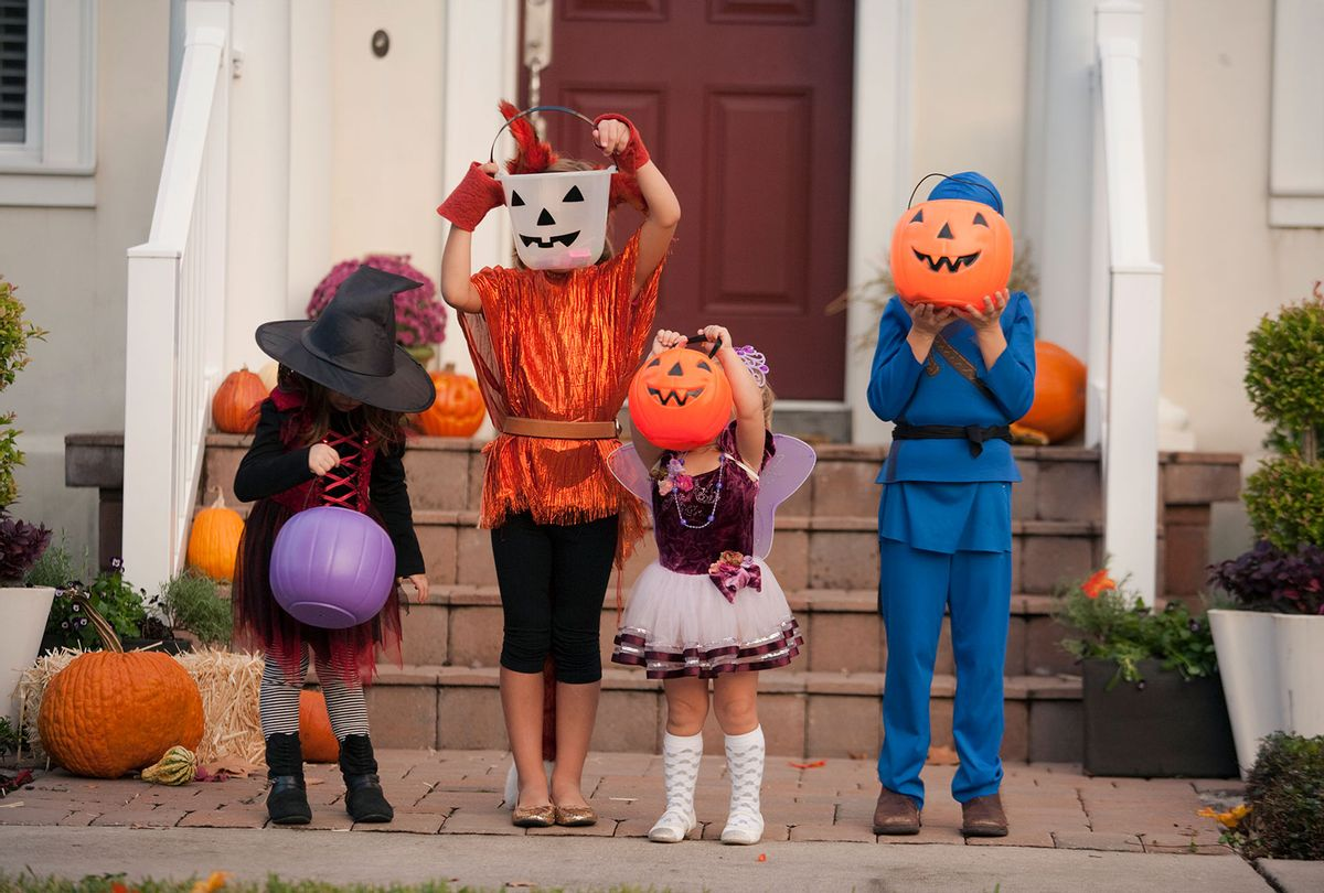 Children covering face with Jack O Lantern bucket in front of house (Getty Images)