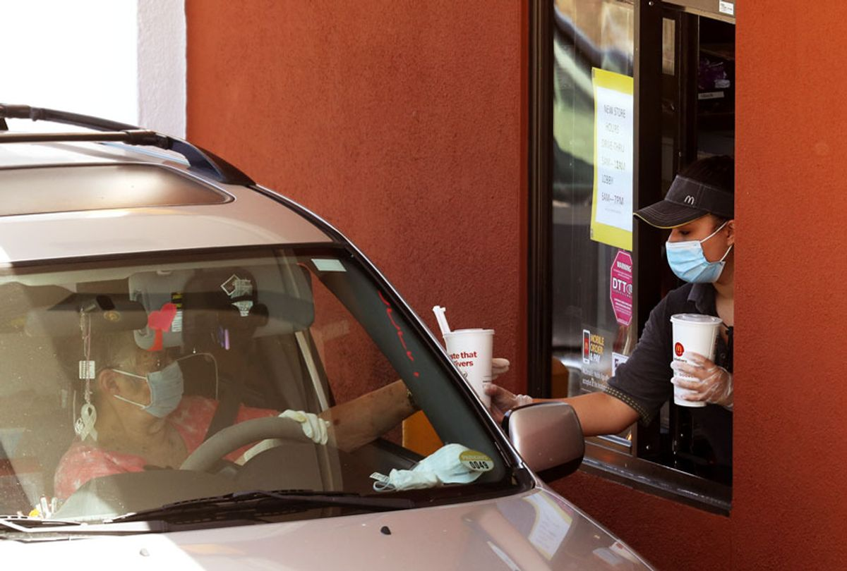 A worker wears a mask and gloves as she hands soft drinks to a customer at a McDonald's drive-thru on April 22, 2020 in Novato, California. (Justin Sullivan/Getty Images)