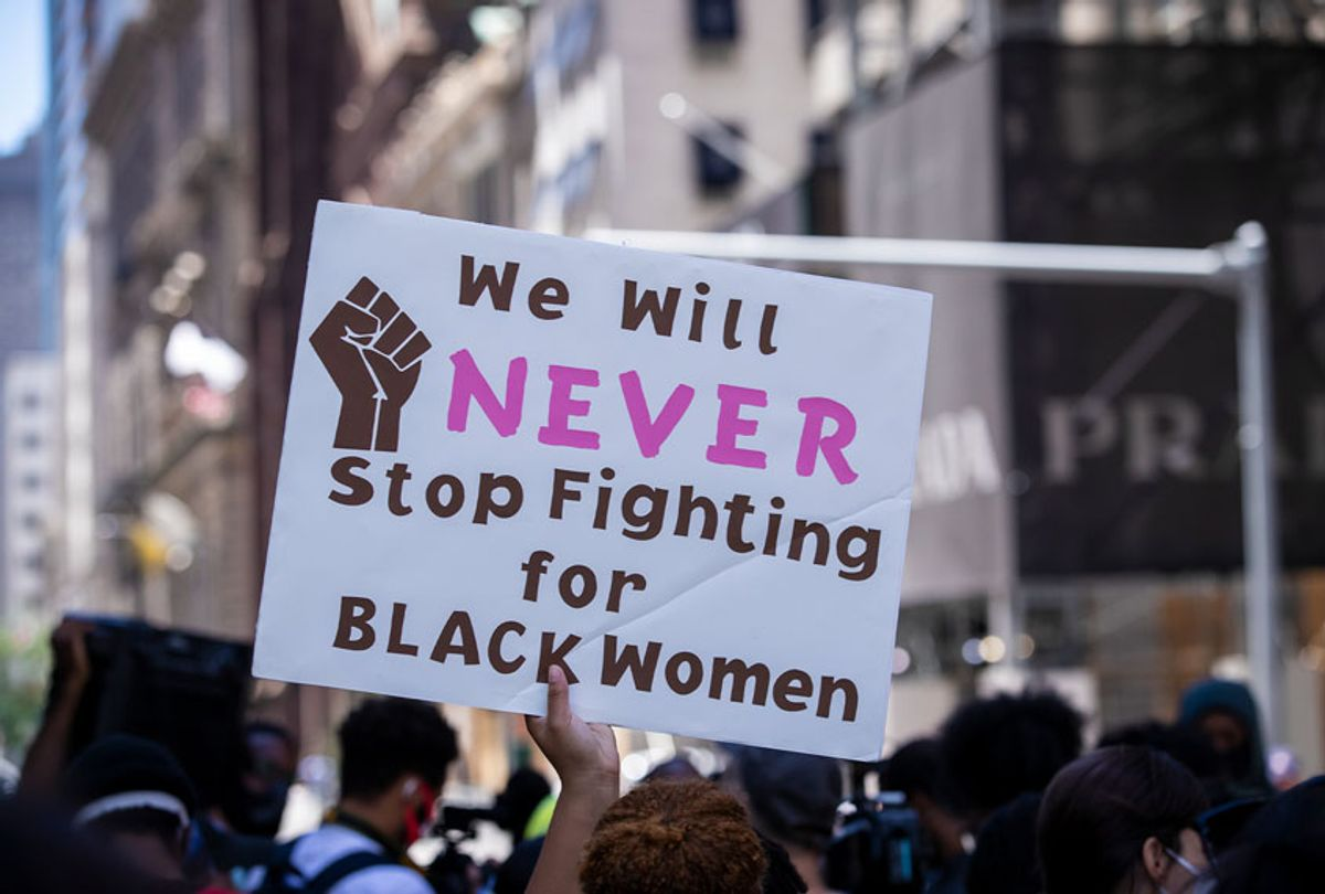 """A protester holds up their homemade sign that says, """"We Will NEVER Stop Fighting for BLACK Women"""" with a picture of the black power fist on the sign during a protest at Trump Tower. This was part of the Black Womxn's Empowerment March that started at Trump Tower and marched to Gracie Mansion. (Ira L. Black/Corbis via Getty Images)"""