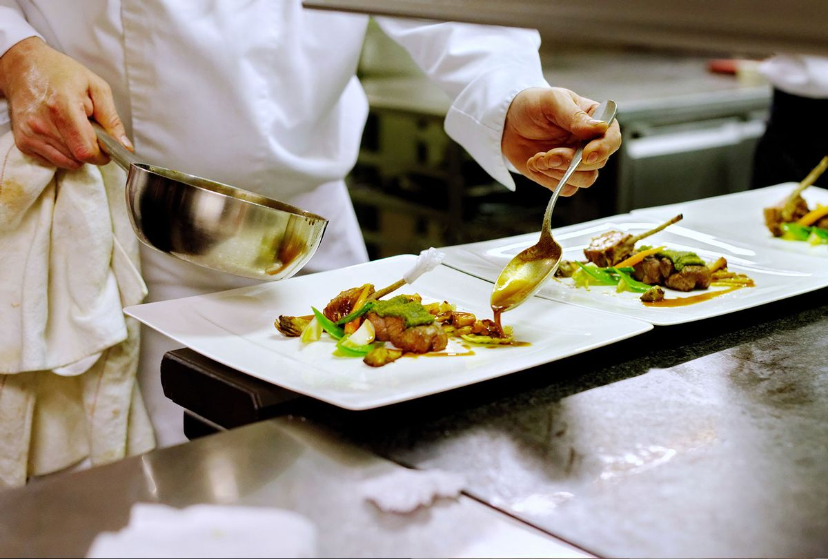 Chef saucing dishes in restaurant kitchen (Getty Images)