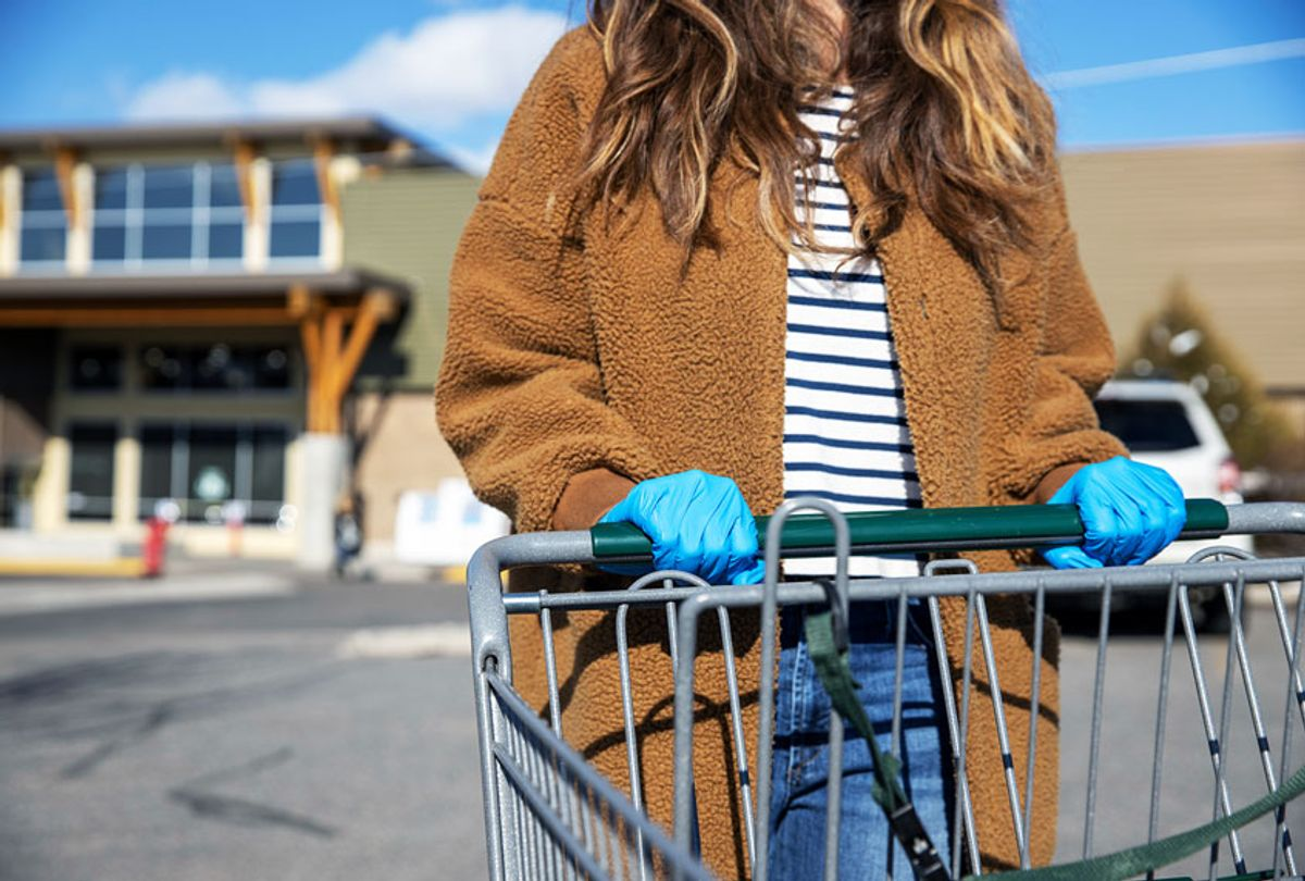 A woman wearing blue latex gloves and pushing a shopping cart during the COVID-19 quarantine (Getty Images)