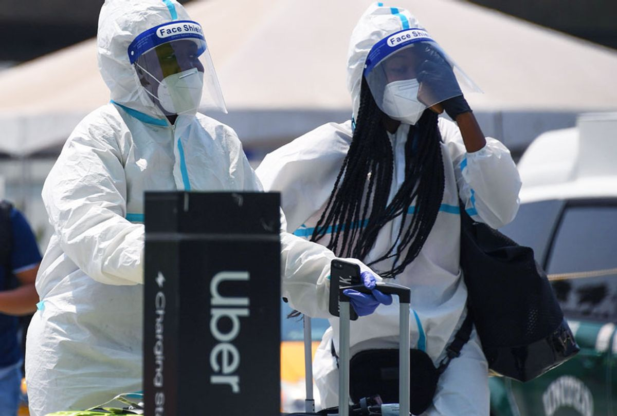 Travelers wearing protective suits, facemasks, face shields and gloves walk past an Uber pick up area August 20, 2020 at Los Angeles International Airport in Los Angeles, California.  (ROBYN BECK/AFP via Getty Images)