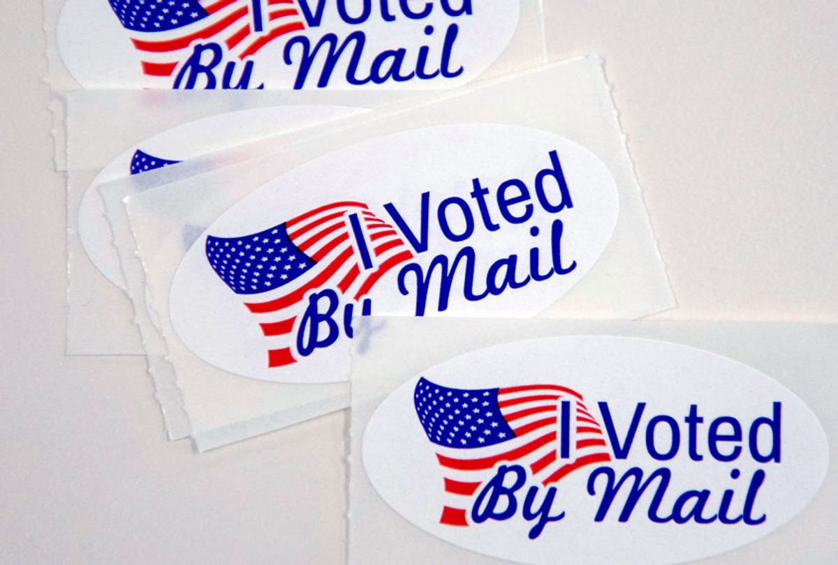 """Stickers that read """"I Voted By Mail"""" sit on a table waiting to be stuffed into envelopes by absentee ballot election workers at the Mecklenburg County Board of Elections office in Charlotte, NC on September 4, 2020 (LOGAN CYRUS/AFP via Getty Images))"""