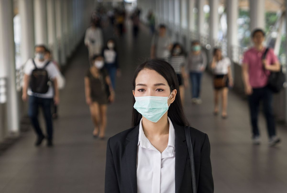 Woman with protective face mask in the urban bridge in city against crowd of peopl (Getty Images)