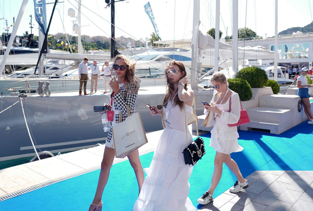 People walk by yachts moored at the Hercules Port in Monaco on September 25, 2019 during the 28th edition of the International Monaco Yacht Show. - The Monaco Yacht Show is considered the most prestigious pleasure boat show in the world with the exhibition of 500 major companies in luxury yachting and featuring over a hundred super and megayachts. (VALERY HACHE/AFP via Getty Images)