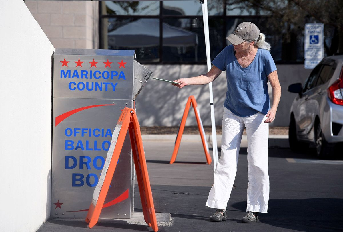 People deposit their mail-in ballots for the US presidential election at a ballot collection box in Phoenix, Arizona on October 18, 2020. (Joe Raedle/Getty Images)