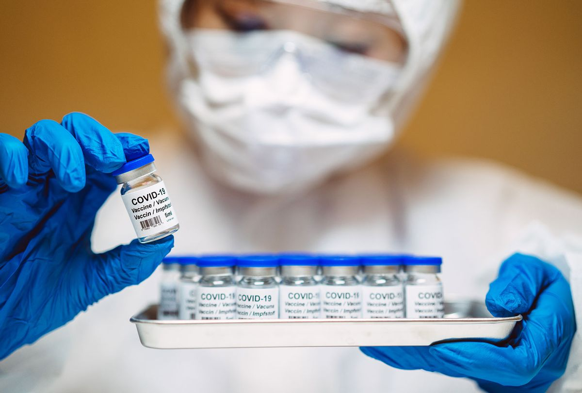 Healthcare professional in protective gloves & workwear holding & organizing a tray of COVID-19 vaccine vials (Getty Images)
