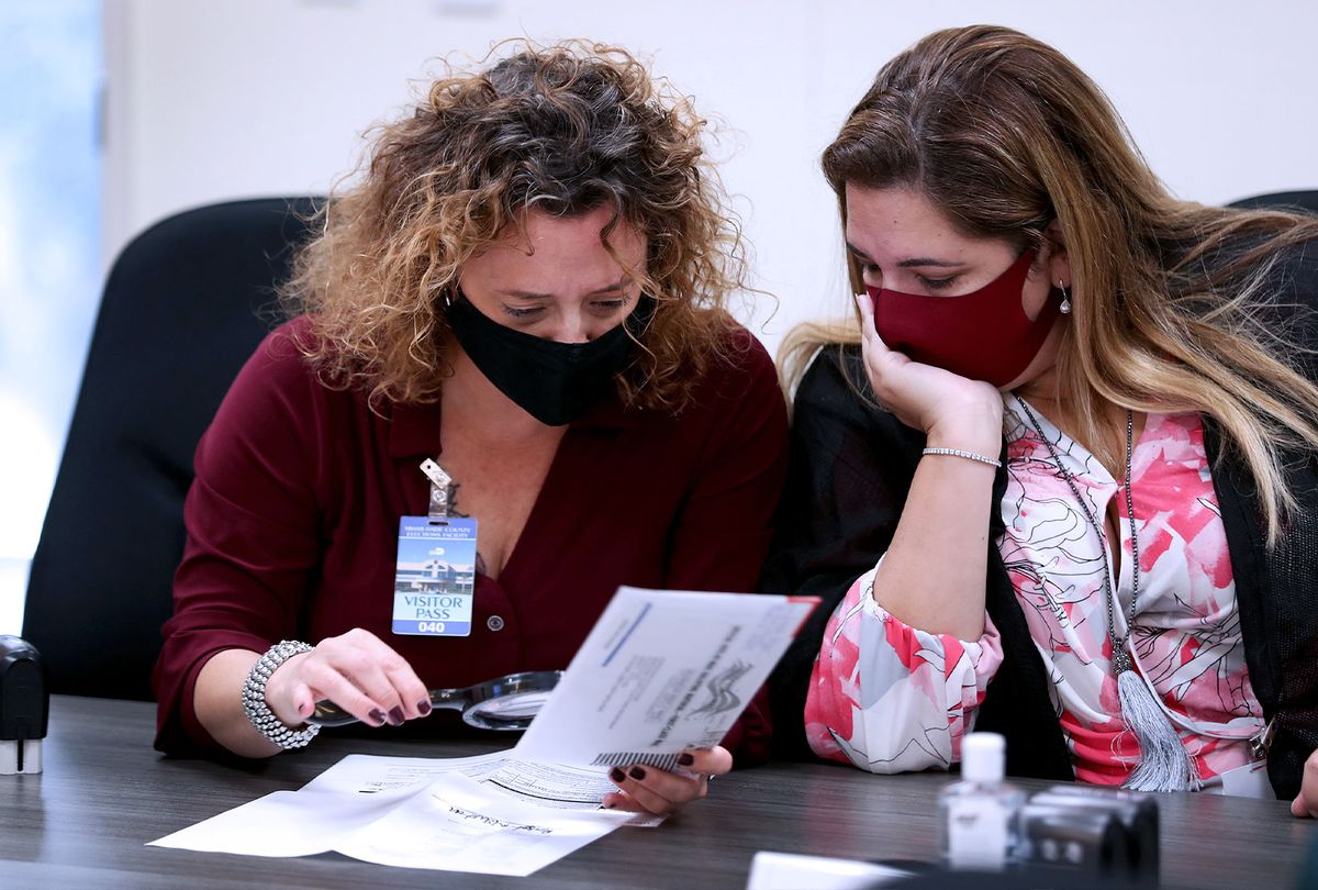 Milena Abreu, County Judge, and Victoria Ferrer, County Judge, inspect a Vote-by-Mail ballot for a valid signature as Miami-Dade County Canvassing Board convenes ahead of the November 3rd general election at the Miami-Dade County Elections Department on October 15, 2020 in Doral, Florida. (Joe Raedle/Getty Images)