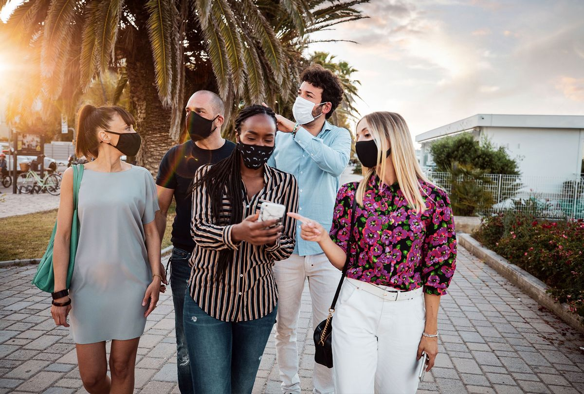 Group of friends meeting in the city wearing protective face masks (Getty Images)