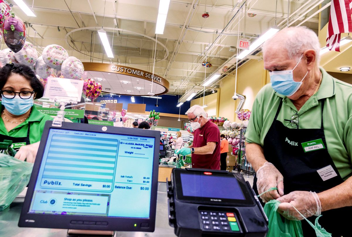 Miami Beach, Publix check out cashier and bagger wearing PPE. (Jeffrey Greenberg/Education Images/Universal Images Group via Getty Images)