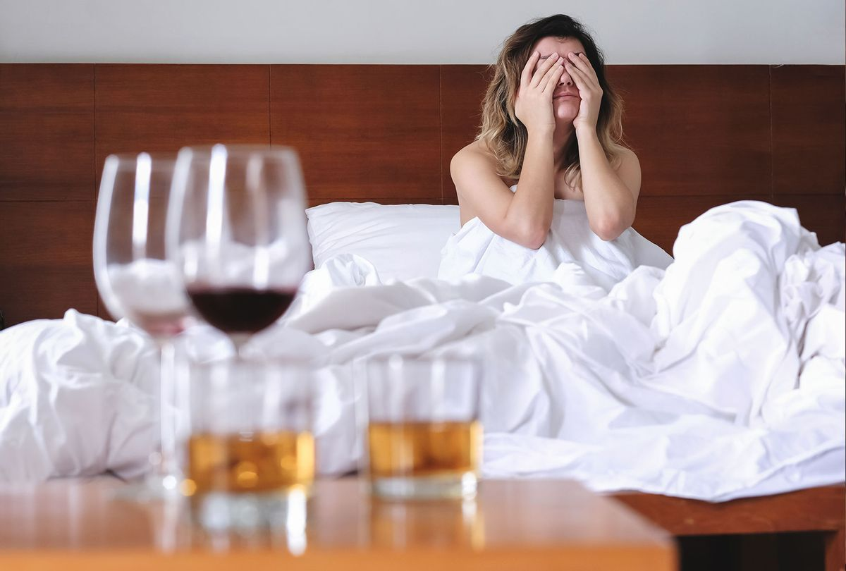 Young exhausted and wasted woman waking up suffering headache and hangover after drinking alcohol lying on bed sick and miserable still drunk (Getty Images)