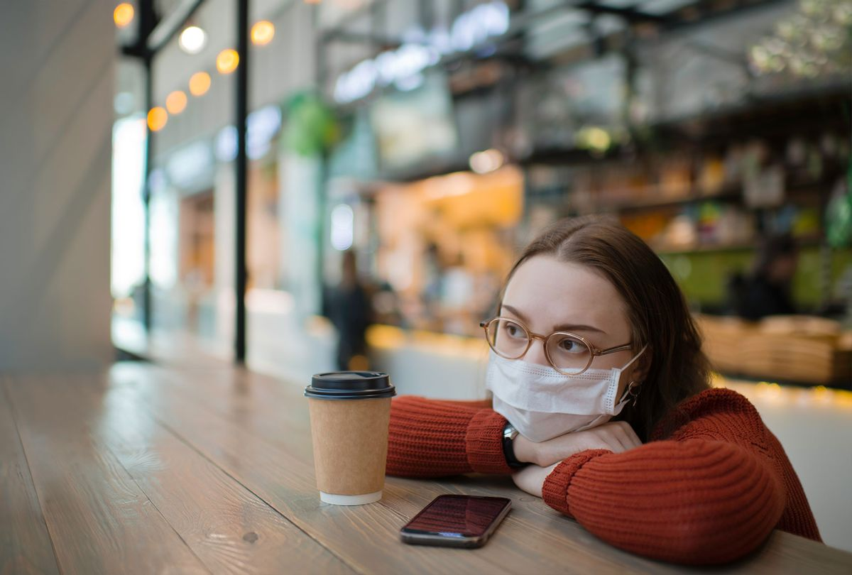 Teenager wearing medical mask protecting herself against virus in a food court of a shopping mall or airport lobby with reusable coffee cup (Getty Images)